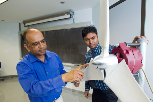 UM-Flint Mechanical Engineering Professor Quamrul Mazumder and student Saiful Siddique examine a wind turbine