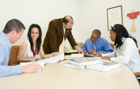 Dr. Kandogan (standing) working with UM-Flint School of Management students