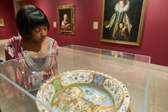 UM-Flint student examines artifact at Flint Institute of Arts