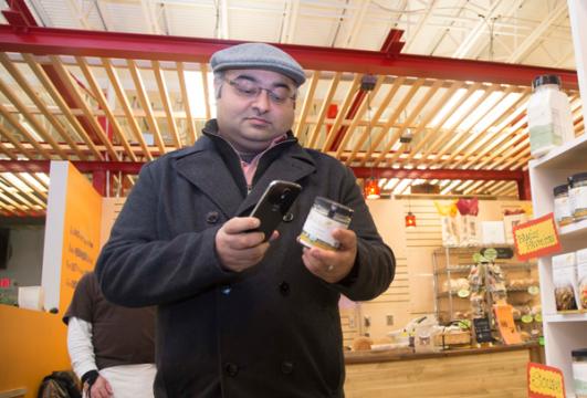UM-Flint associate professor of marketing Sy Banerjee uses his smart phone while shopping.