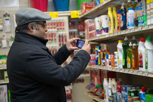 Banerjee takes a picture of products on a shelf.