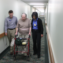 Physical therapy student and professor lead senior community resident down hallway
