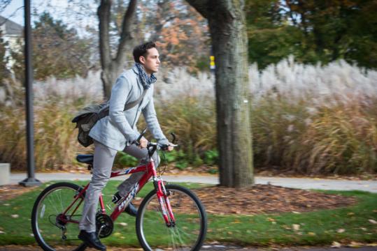 UM-Flint student rides bike down Kearsley Street.