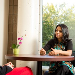 Women's Education Center director Rushika Patel, PhD talks with a UM-Flint student.