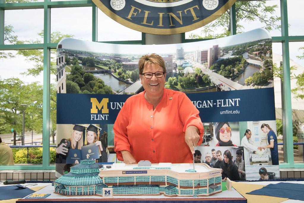 Chancellor Susan E. Borrego cuts a cake shaped as a replica of UM-Flint's University Pavilion.