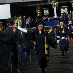 UM-Flint graduates high-five.