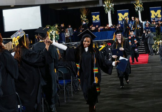 UM-Flint graduates high-five.