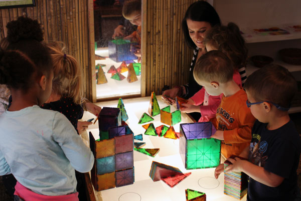 ECDC Assistant Director Joslyn Marinelli assists children building structures with colored tiles.