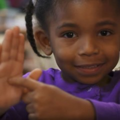 UM-Flint Early Childhood Development Center youngster shows where Flint is on her palm.