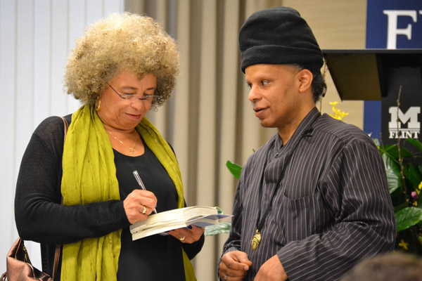 Angela Davis signs a book for a faculty forum participant at UM-Flint.