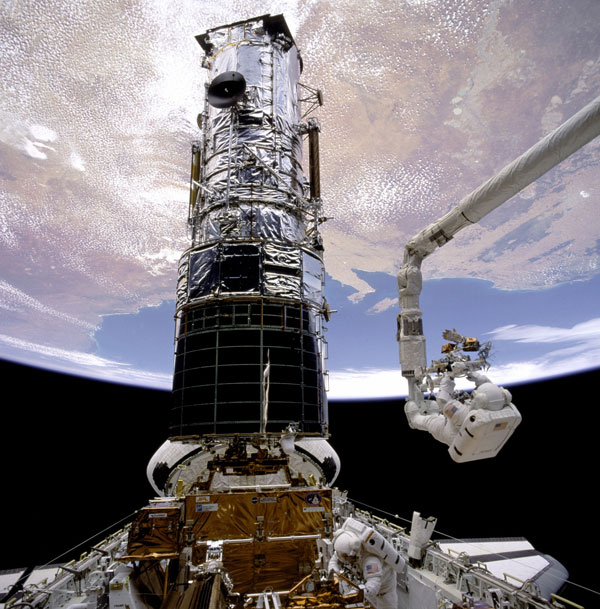 Story Musgrave helping to repair Hubble Telescope.