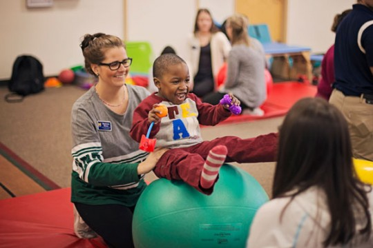 UM-Flint PT students working with child from University's Early Childhood Development Center