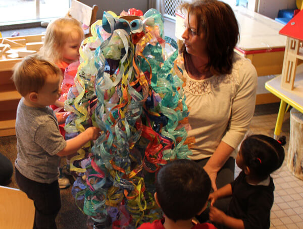 Children admire the colors of their developing chandelier with Diana Hensley, head teacher.