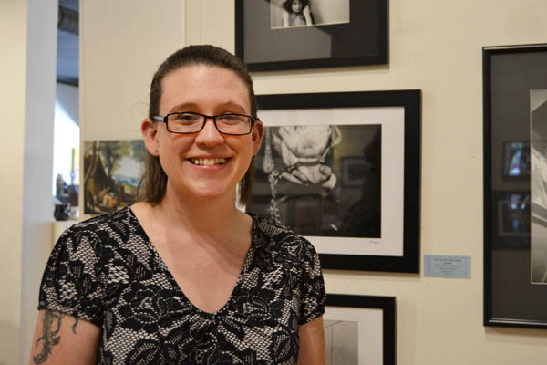 "Breanna Kerrison stands with her photograph ""Bits and Pieces"""