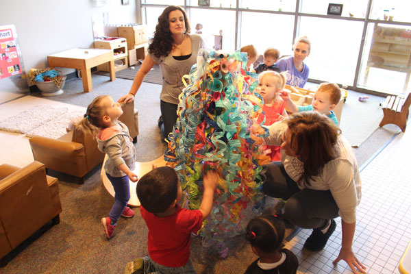 Toddlers at UM-Flint's Early Childhood Development Center creating their Chihuly-inspired chandelier.