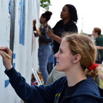 UM-Flint Visual Art students paint murals along Saginaw Street in Flint.