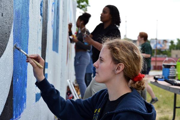 UM-Flint Visual Art students paint murals along Saginaw Street in Flint.