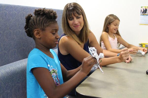UM-Flint Graduate student Amanda Brecht guides kids in a fun pre-writing activity.
