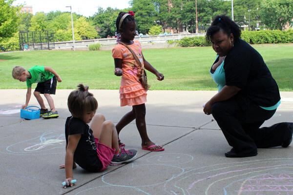 UM-Flint Graduate student Starletta Rett-Henry uses a chalk activity with kids to spark ideas.
