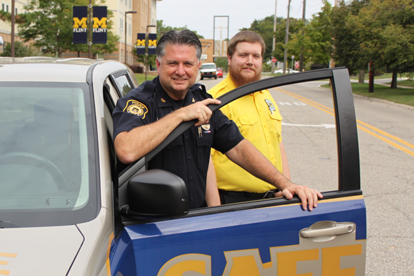 UM-Flint Public Safety Chief Ray Hall and student safety patrol member Matthew July.