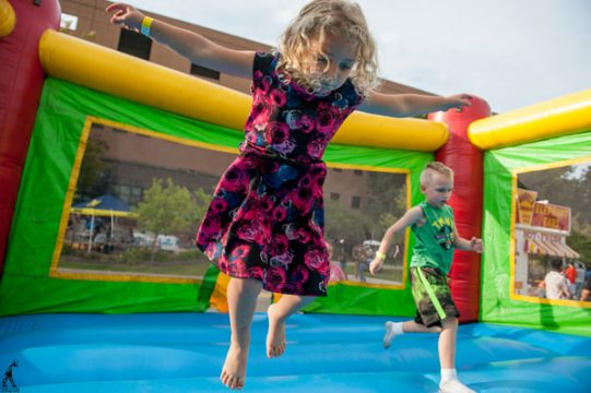 Children play in a bounce house on the UM-Flint campus