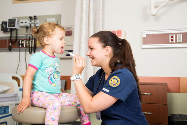 UM-Flint nursing student with young patient.