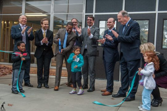 Educators and legislators cut ribbon to open new early childhood center.