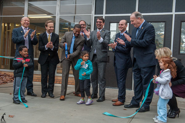 Educators and legislators cut ribbon to open new early childhood center.