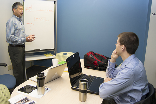 Adil Mohammed works with student Charles Herzog to develop healthcare software in the UM-Flint Innovation Incubator.