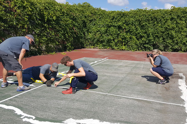 Skye Whitcomb captures high school students repairing tennis courts at their high school during her Um-Flint Communication internship