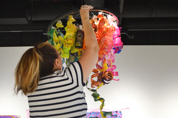 Melissa Laeaym-Fernandez hangs a piece created from recycled water bottles in the UM-Flint Art Gallery