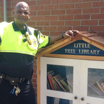 UM-Flint public safety office Mark Walker stands near DPS' new Little Free Library.