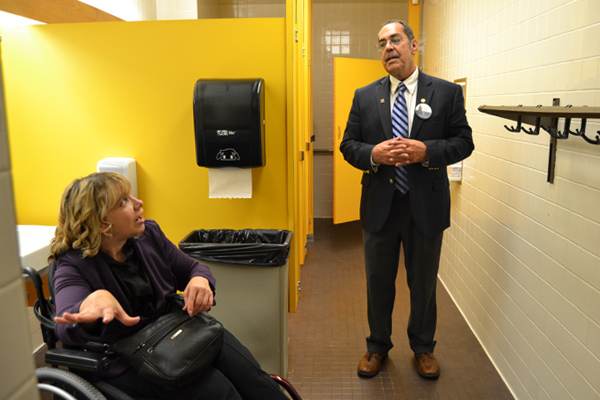 Lizotte (left) explains issues that can arise for wheelchair users in public bathrooms to State Representative Tim Sneller during his Take Your Legislator to Work Day visit.