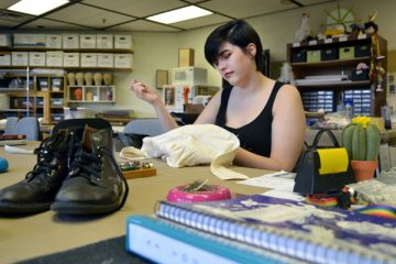 Quill Neuville of UM-Flint Theatre and Dance working in the Costume Shop