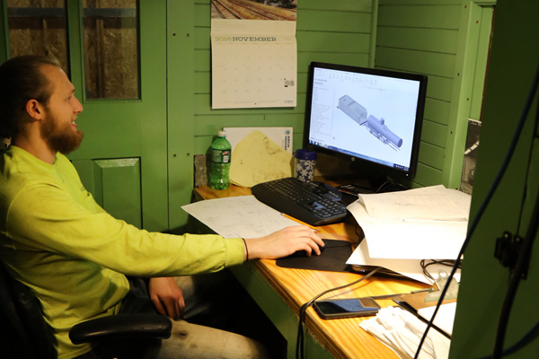 Uriah Horton creating CAD drawings in his caboose office inside the Huckleberry Railroad Locomotive Repair Shop.