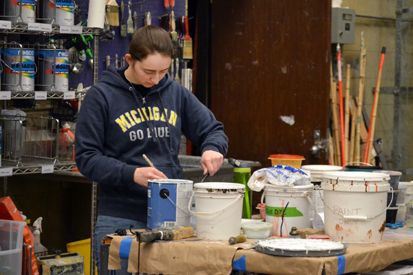 UM-Flint Theatre student Sarah Briggs mixing paint in the Scene Shop