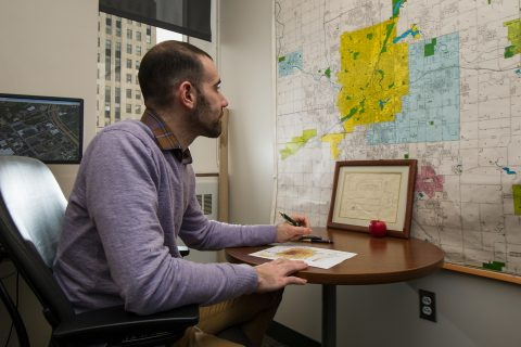 Richard Sadler, in his office, referencing map of Flint and Genesee County.