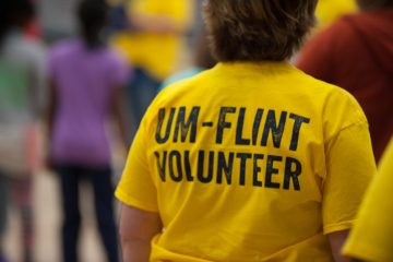A member of the campus community volunteering at a UM-Flint event.
