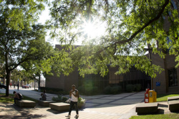 Student walking in front of French Hall with the sun peering through the trees