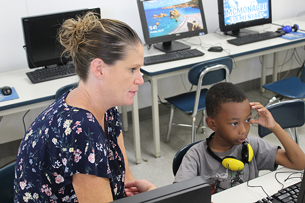 Kristie Yammine, Literacy Education (MA) graduate and literacy coach at McMonagle Elementary in Flint, works with a student.