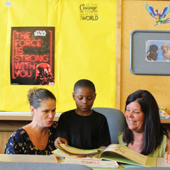 Literacy Education (MA) graduates Kristie Yammine (left) and Diane Richards (right) work with a student at McMonagle Elementary in Flint.