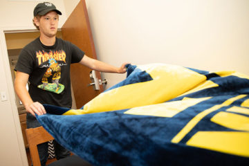 A student is placing a blanket on his bed in his dorm room.