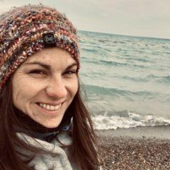 Nicole Stuckey takes a photo by a lake.