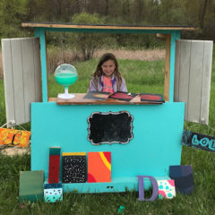 A third-grade girl sells artwork at her art stand.