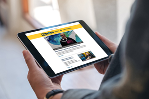 image of woman's hands holding black tablet pc with UM-Flint NOW newsletter on the screen