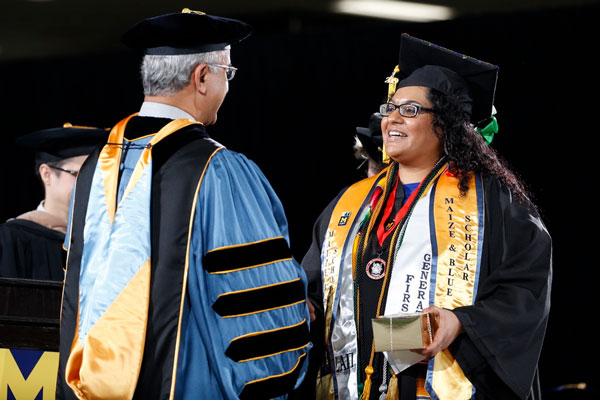 Adelina Gutierrez receives congratulations from Chancellor Dutta upon graduating with her degree in public health.
