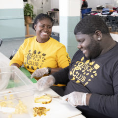 Two UM-Flint students and members of the Block Club slices pineapples during a volunteer event for More than a Day.