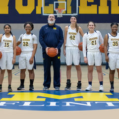 Seven members of the UM-Flint Women's Club Basketball Team and their coach pose for a portrait in the Recreation Center.