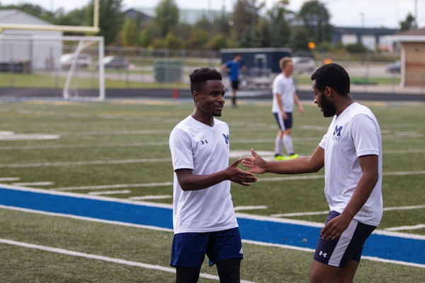 Two UM-Flint Men's Club Soccer players high five each other during practice.