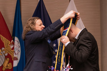 Helen Budd places stole on on graduate at Veterans' Graduation Dinner. (Photo by UM-Flint)